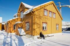 L'homme s'assied devant le vieux bâtiment en bois de Skansen dans Tromso, Norvège Images stock