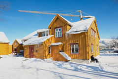 L'homme s'assied devant le vieux bâtiment en bois de Skansen dans Tromso, Norvège Photographie stock
