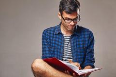 L'homme s'assied et des notes dans un carnet Image libre de droits