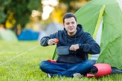 L'homme s'assied par la tente avec la casserole dans sa main dans le secteur de camping Photo stock