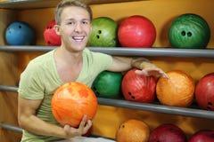 L'homme s'assied près des étagères avec des billes dans le club de bowling Images stock