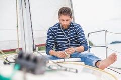 L'homme s'assied sur l'arc du yacht de navigation et tient le pot photos libres de droits