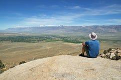 L'homme s'assied sur la roche donnent sur images stock