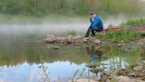 L'homme s'assied sur le bateau à la berge calme en cristal avec le brouillard épais banque de vidéos