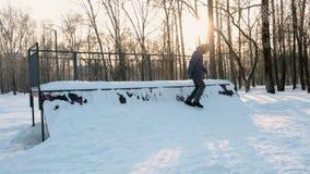 L'homme s'assied sur le parc d'embarquement de patin dans la neige Dérives de neige sur la colline à faire de la planche à roulet banque de vidéos