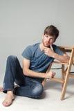 L'homme s'assied sur le plancher images libres de droits