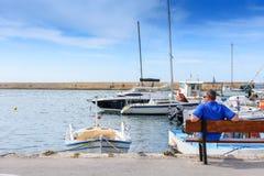 L'homme s'assied sur un banc dans le port et attend la fille sur un fond des yachts et des bateaux blancs Photos libres de droits