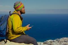 L'homme s'assied sur une falaise au-dessus de la mer avec un smartphone à disposition Image stock