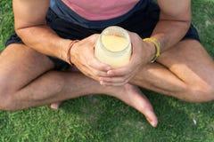 L'homme s'assied sur une herbe dans le pays tropical de l'île Samui, le smoothie de boissons d'homme Photographie stock libre de droits