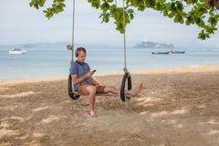 L'homme s'assied sur une oscillation et écoute la musique Concept de mode de vie La Thaïlande, Krabi Février 2017 Images stock