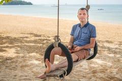 L'homme s'assied sur une oscillation et détend Concept de mode de vie La Thaïlande, Krabi Février 2017 Photos libres de droits