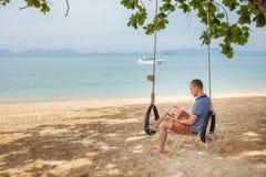 L'homme s'assied sur une oscillation et lit un eBook Concept de mode de vie La Thaïlande, Krabi Février 2017 Photos libres de droits