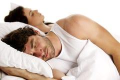 L'homme s'est étendu dans le lit blanc à côté d'un sommeil de femme Images libres de droits