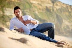 L'homme s'est étendu sur le sable Image stock