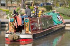 L'homme s'est assis sur la poupe du narrowboat brillamment coloré de canal Image stock