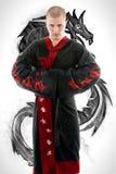 L'homme s'est habillé dans le kimono noir de dragon démontrant les arts martiaux Co photo libre de droits