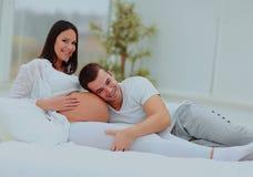 L'homme s'est penché contre à la bosse de bébé de son épouse enceinte, qui se trouve sur le lit Images libres de droits