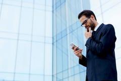L'homme sûr dans un costume élégant se tient près d'un haut immeuble de bureaux moderne avec un téléphone dans sa main Photos libres de droits