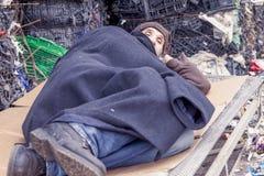 L'homme sans abri dort dans les déchets photos libres de droits