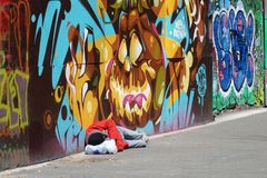 L'homme sans abri dort devant la peinture murale de graffiti dans l'East Village, New York City Photographie stock libre de droits