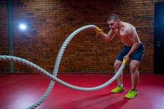 L'homme sans chemise musculaire dans un gymnase s'exerce avec des cordes de bataille pendant sa formation à haute intensité d'int Photographie stock