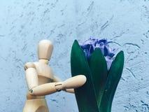 l'homme sans visage en bois donne les fleurs bleues photo libre de droits