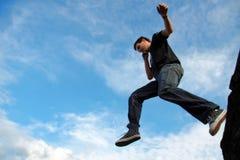 L'homme sautant à partir du bord en pierre Photographie stock libre de droits