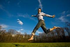 L'homme sautant dans un domaine Image libre de droits