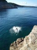 L'homme sautant en mer Photographie stock libre de droits