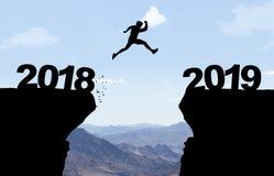 L'homme sautant par-dessus l'abîme avec le texte 2018/2019 images libres de droits