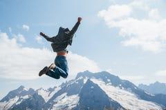 L'homme sautant sur la montagne images stock