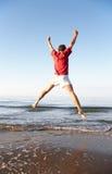 L'homme sautant sur la plage photo libre de droits