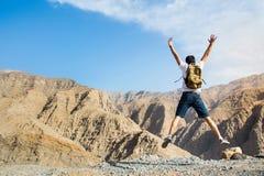 L'homme sautant sur le dessus de montagne photographie stock