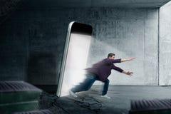 L'homme saute d'un écran rougeoyant de smartphone Photographie stock libre de droits