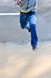 L'homme saute par-dessus la route inondée Photographie stock libre de droits