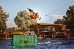 L'homme saute par-dessus un tremplin sur l'eau Image stock