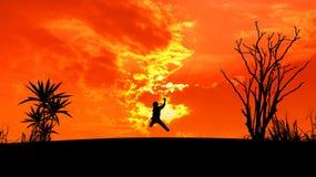 L'homme sautent la silhouette au coucher du soleil photographie stock libre de droits