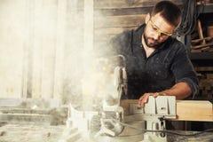 L'homme scie un conseil en bois Photos libres de droits