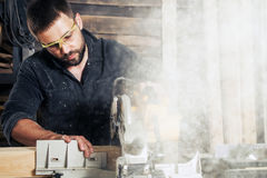 L'homme scie un conseil en bois Image stock