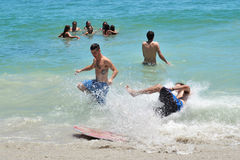 L'homme se brise dans la vague pendant qu'il écrèment des conseils dans l'océan Image libre de droits