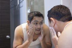 L'homme se lavent le visage dans la salle de bains images libres de droits