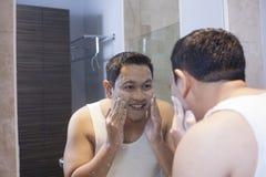 L'homme se lavent le visage dans la salle de bains photos stock