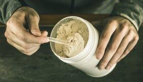 L'homme se met une partie de scoop de protéine de lactalbumine Folâtre la nutrition image stock