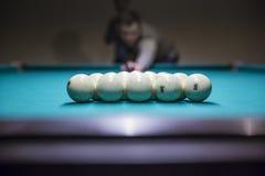 L'homme se préparent dedans au jeu de début des boules de billard avec la triangle Image stock