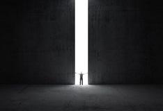 L'homme se tient à la lumière de l'ouverture photographie stock libre de droits