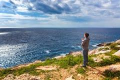L'homme se tient au bord de l'abîme et regarde la mer photos libres de droits