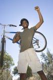 L'homme se tient avec le bras augmenté tenant le vélo de montagne Images stock