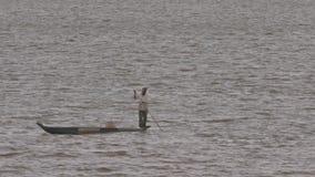 L'homme se tient dans des rangées de canoë de pirogue avec le bâton sur le lac banque de vidéos