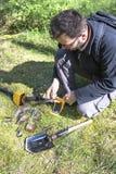 L'homme se tient dans sa main qu'un objet a trouvée dans la terre Un détecteur de métaux et une pelle se trouvent à côté de lui photographie stock libre de droits