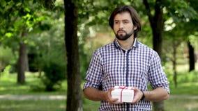 L'homme se tient en parc et tient un présent Il le secoue L'homme regarde aux left and right et à ses montres en main clips vidéos